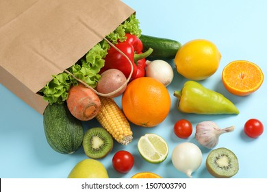 Paper bag, vegetables and fruits on blue background, space for text