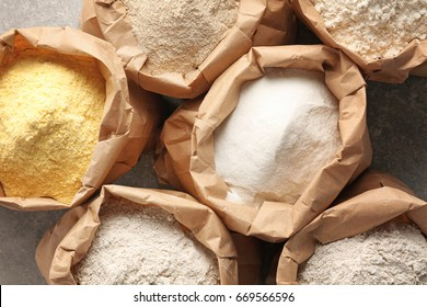 Paper bags with different types of flour on gray background, closeup