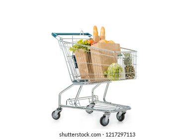 paper bags full of products in shopping trolley isolated on white