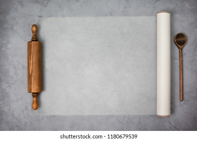 paper for baking, wooden rolling pin on a gray concrete background. view from above. copy space