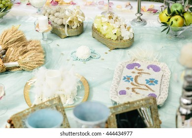Paper balls and blue necklaces lie on a table with sweets
