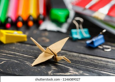 Paper bird on the table among markers, notebooks, clips and sharpeners. Flat lay.