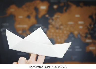 Paper boat against map of the world