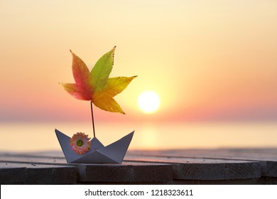 paper boat with autumn leaves sail at the beach