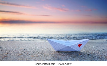 paper boat at the beach - romantic summer sunset
