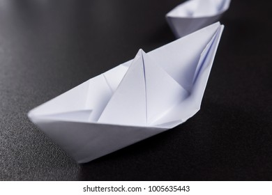 Paper boat close-up on black background. Origami ship paves the way.