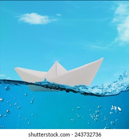 paper boat floating among the waves in the ocean. origami boat floating in the water.