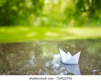Paper boat floating in a puddle