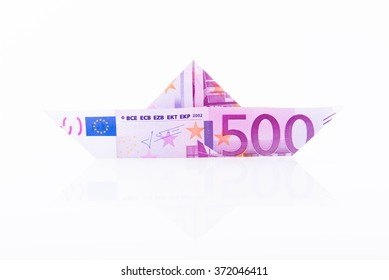 Paper boat made with a 500 euro note on white background