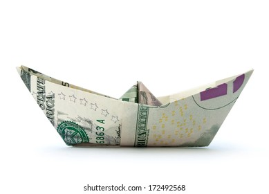 Paper boat made from dollar banknotes over a white background