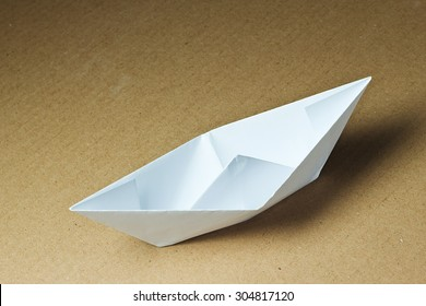 Paper boat on a cardboard background..