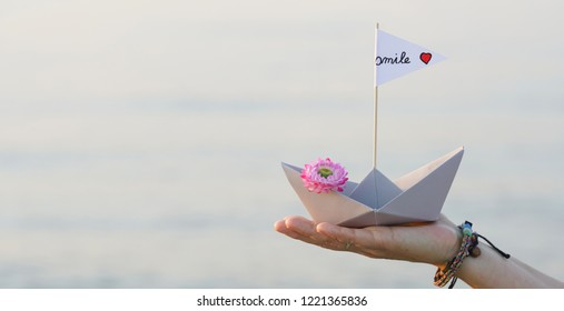 paper boat on womans hand - enjoy the moment