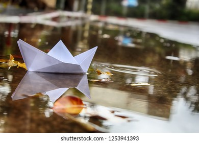 Paper Boat (Origami Ship) sails in a puddle formed after rain. Winter in Israel, December
