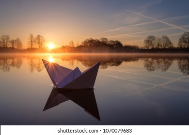 A paper boat sailing along the river at dawn.