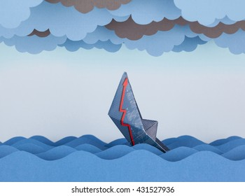 Paper boat is sinking into paper sea. Paper waves and clouds. Concept of crisis and economic collapse.