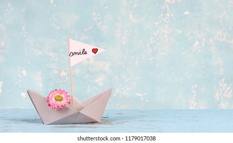 paper boat with smile sail - travel concept