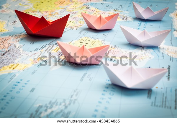 Paper boats following a red leader boat on world map. Concept for leadership, teamwork and winning success