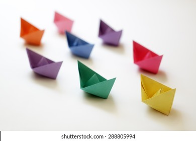 Paper boats of multi-colour following a leader boat concept for leadership, teamwork and winning success