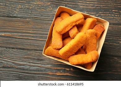 Paper box with cheese sticks on wooden background