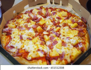 A paper box of delicious and color pizza Hawaiian with bacon, ham, pineapple and mozzarella cheese.