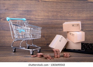 Paper boxes, shopping cart and computer keyboard on wooden background. Selling goods or services online over the internet
