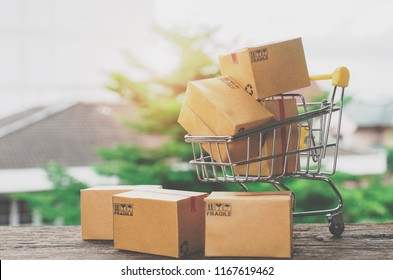 Paper boxes in a shopping cart on wood table.Easy shopping with finger tips for consumers.Online shopping and delivery service concept.