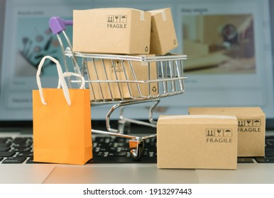 Paper boxes in a trolley and shopping bag on laptop computer ,Online shopping or ecommmerce concept