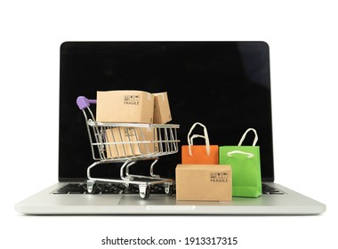 Paper boxes in a trolley and shopping bag on laptop computer on white background,Online shopping or ecommmerce concept