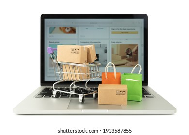 Paper boxes in a trolley and shopping bag on laptop computer isolated on white background,Online shopping or ecommmerce concept