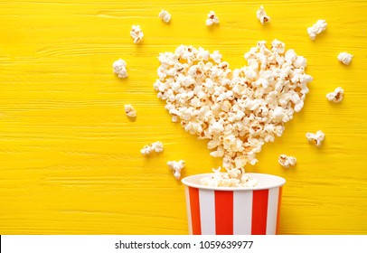 Paper bucket and heart made of tasty popcorn on color wooden background