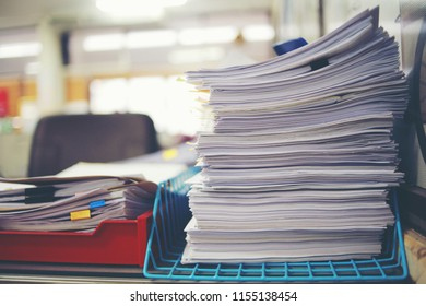 Paper business documents of unfinished stacked on office desk archive,in archive analyzing the market and considers on the size of future profits on table office.
