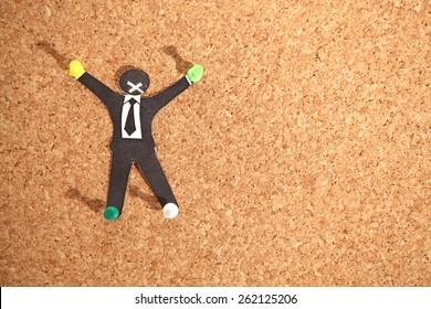 Paper businessman crucified on office corkboard