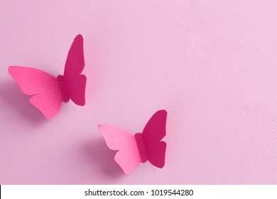 Paper butterflies on a pink background. Love and Valentine's day concept. Top view
