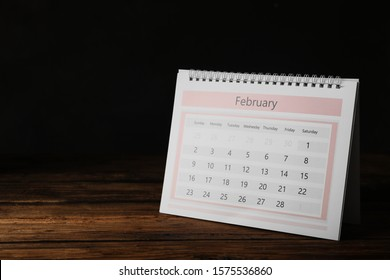 Paper calendar on wooden table, space for text. Planning concept