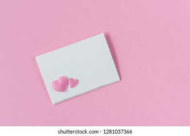 Paper card mockup on pink background with two hearts. Top view. Flat lay. Love confession