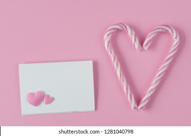 Paper card mockup on pink background with hearts. Two candy canes making a heart. Top view. Flat lay. Love confession.