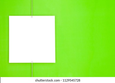 Paper card (photo frame) hanging on metal rope with magnets on green background