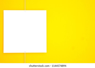 Paper card (photo frame) hanging on metal rope with magnets on yellow background