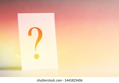 Paper card with a question mark on a gray background, concept.