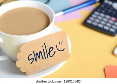 """Paper card with """"smile"""" text and coffee with calculator on white wooden background"""