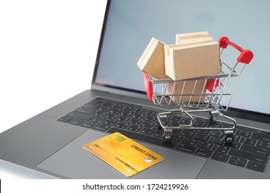 Paper cartons or parcel in cart and credit card on laptop keyboard. Shopping service on online web and offers home delivery. online shopping concept.