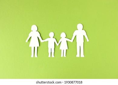 Papierkettenfamilie, die auf hellgrünem Hintergrund ausgeschnitten ist