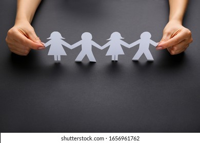 Paper chain people with female hands on black background