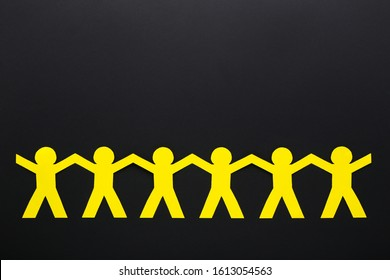 Paper chain people on black background