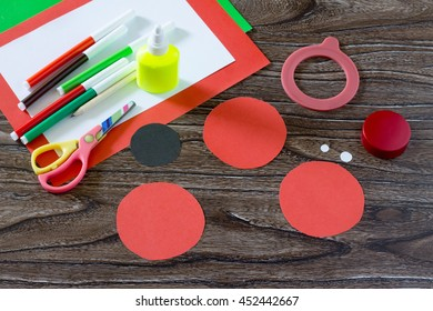 Paper circles, sheets of paper, markers, scissors on a wooden table. Paper ladybug craft for children. Children's art project.