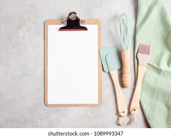 Paper clipboard with empty space and kitchen utensils top view. Cooking blog, classes and recipe text
