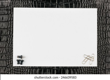 Paper clips and thumbtacks lying on a white paper on the natural leather