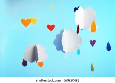 Paper clouds with drops on blue background