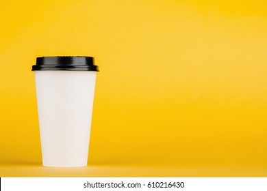 Paper coffee container with black lid on yellow background