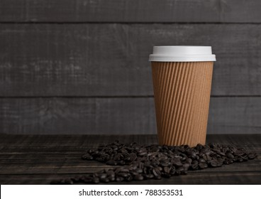 Paper coffee cup with cappuccino and coffee beans on wooden background